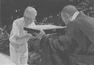代表して写経を奉納する中岡さん(左)。右は山口・金剛峯寺山林部長